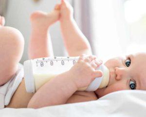 um bebê deixado em cama bebendo leite de formula infantil