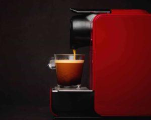cafeteira de cápsula e um copo de café