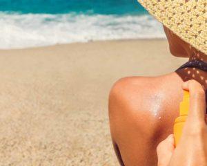 mulher aplicando protetor solar em costa