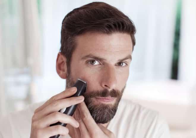 um homem usando barbeador elétrico