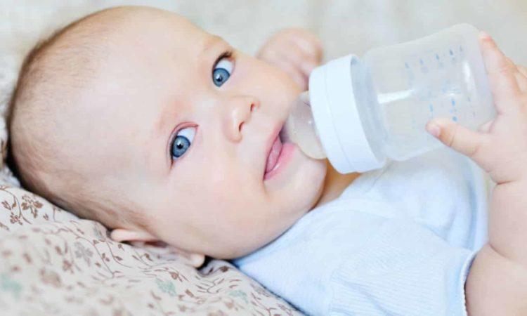 bebê usando mamadeira para beber leite em pó