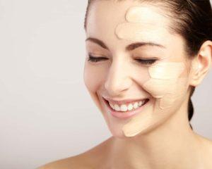 mulher bonita com rosto aplicando base facial