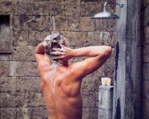 um homem lavando cabelo com shampoos para calvície masculina
