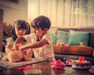 menino e menina brincando com bonecas em sala de estar