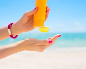 mulher aplicando protetor solar sob sol