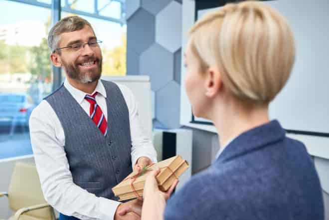 uma colega dá presente para amigo da empresa