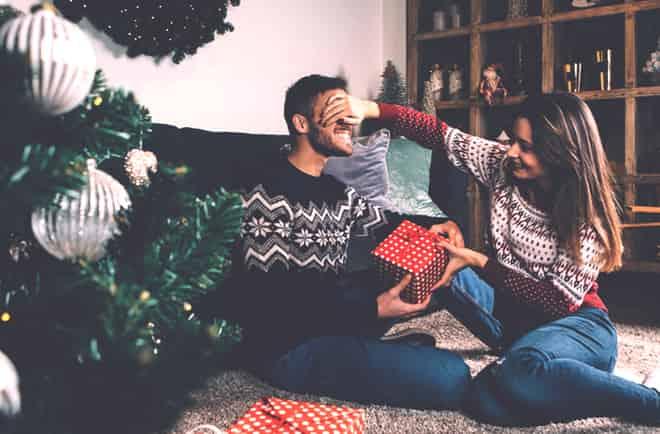 uma garota dá presente de natal para namorado