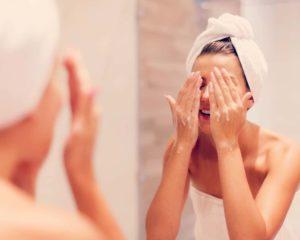 uma mulher limpando rostos com sobonete líquido facial