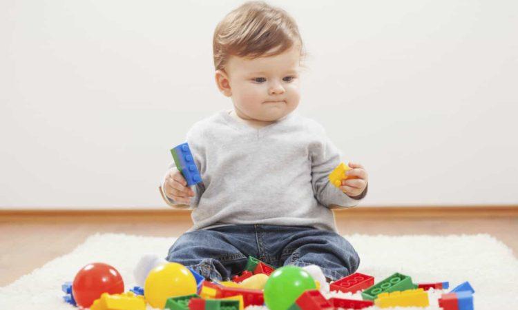 um bebê menino brincando com brinquedos em tapete