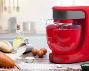 uma batedeira philco de cor vermelhor na mesa, pão e farinha