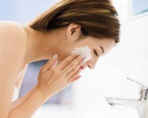 mulher limpando rosto com melhor sabonete