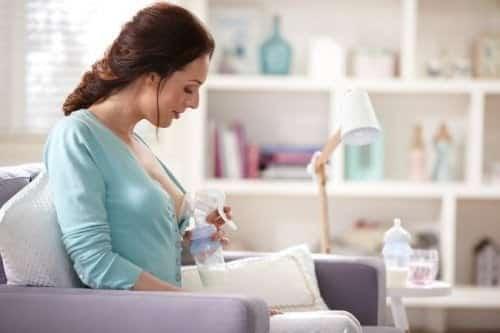 uma mamãe usando bombinha de tira leite