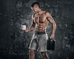 homem com músculos fazendo treinos, academia e tomando wheys isolados