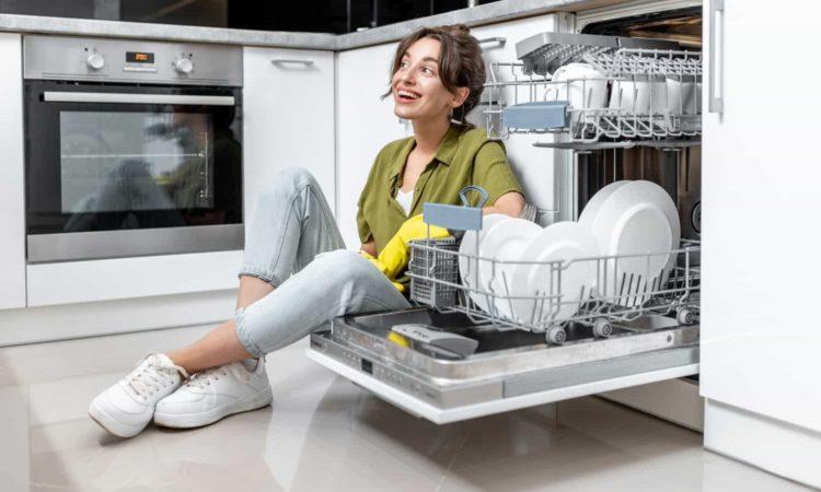 uma mulher em cozinha com lava-louças, pratos