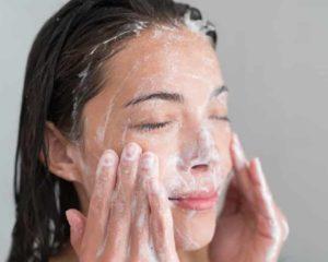 mulher esfregando rosto com esfoliante facial