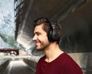 homem ouvindo música com headset bluetooth em subway