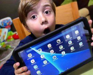 menino levando um tablet infantil com apps instalados