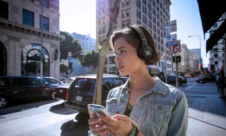 garota na rua ouvindo música com ouvido bluetooth JBL