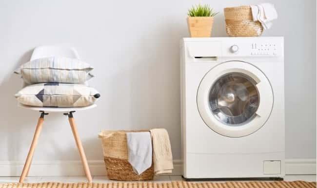 roupas e toalhas na mesa perto de uma maquina de lavar roupa