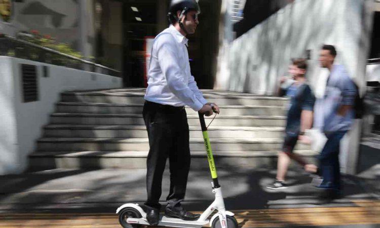 um homem com capacete andando em patinete elétrico na rua