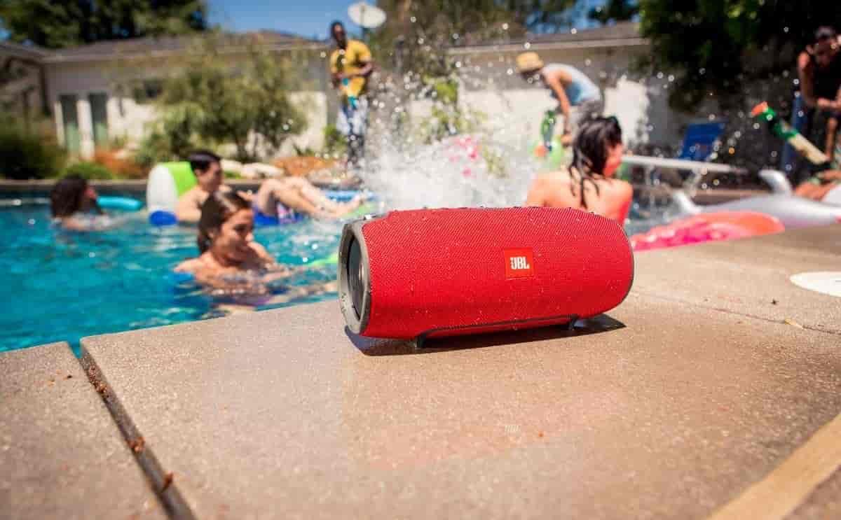 caixa de som jbl vermelho, piscina, pessoas nadando