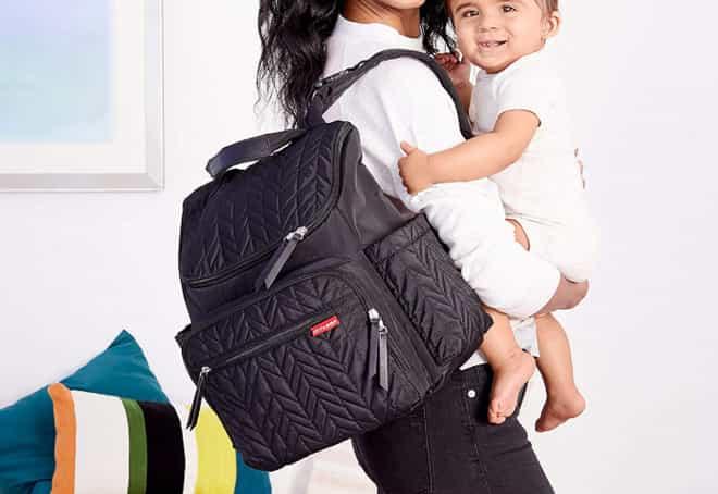 uma mãe com um bebe e bolsa maternidade no ombro