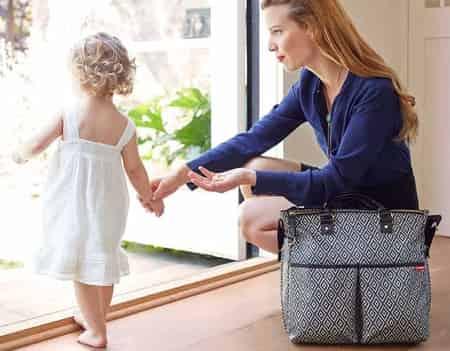 uma mulher e sua filha, uma bolsa ao lado