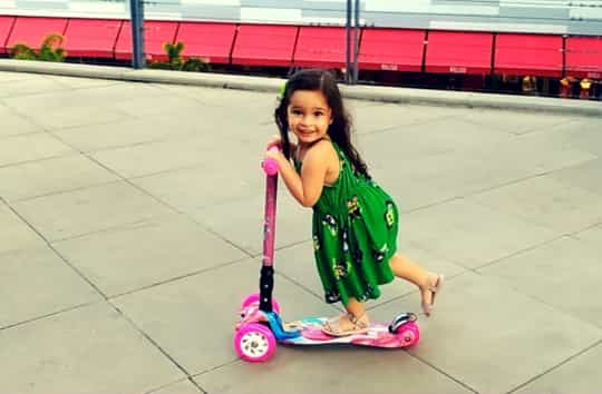 uma menina andando com patinete 3 rodas