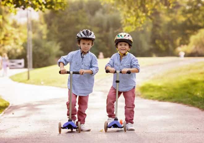 dois meninos andando patinete 3 rodas