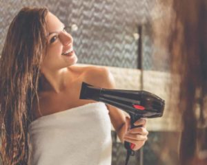 mulher secando cabelo com secador