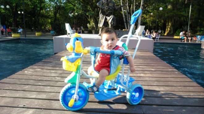 um menino no carrinho de passeio perto da piscina