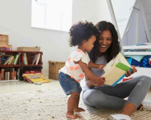 mamãe e filha lendo livre para bebê