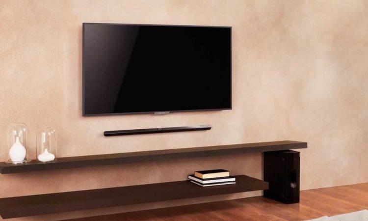 um soundbar embaixo de tv em sala de estar