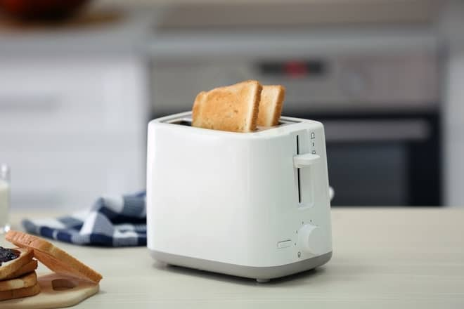 uma torradeira na mesa, com pão