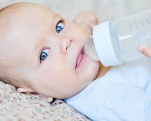 um bebê usando Mamadeira