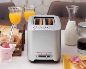 mesa com suco de laranja, torradeira e pão