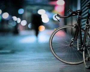 uma bicicleta estacionada ao lado da rua em noite