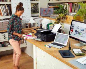 uma secretária usando impressora, notebook e computador perto