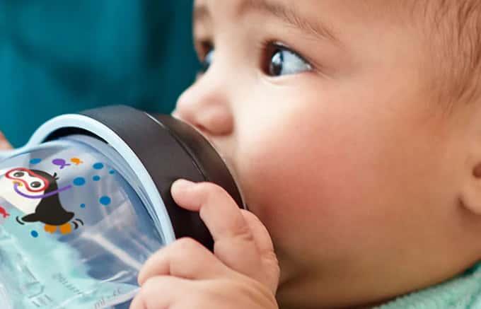um bebe usando Copo de água