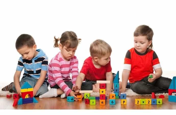4 crianças brincando com brinquedos educativos