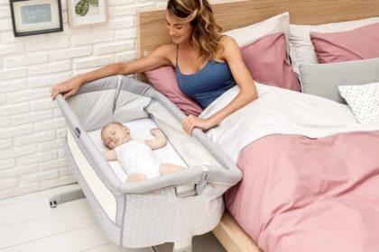 bebê dormindo em berço portátil e mamãe ao perto