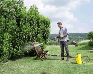 um homen lavando cadeira em jardim