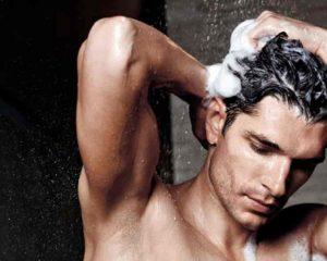 homem lavando cabelo com shampoo para calvície