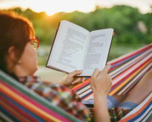uma pessoa lendo livro auto ajuda no parque