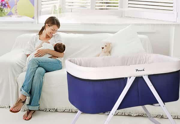 mamãe abraçando bebê, berço portátil e sofa