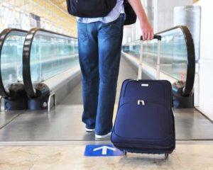 um homem levando mala de viagem em aeroporto