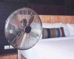 um ventilador ligado, uma cama, em quarto de dormir