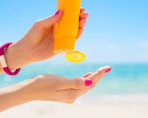 mão aplicando protetor solar