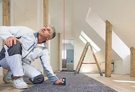 um homem decorando casa, medindo