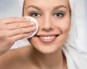 mulher usando demaquilantes para limpar rosto